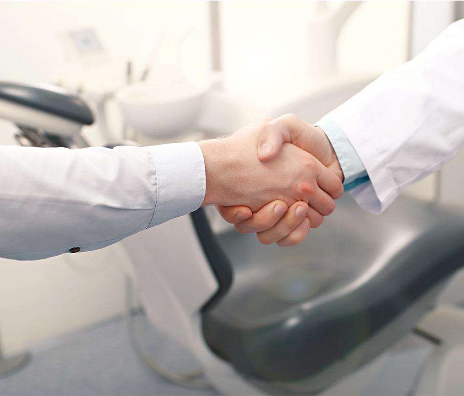 Zahnarzt schüttelt Patient die Hand