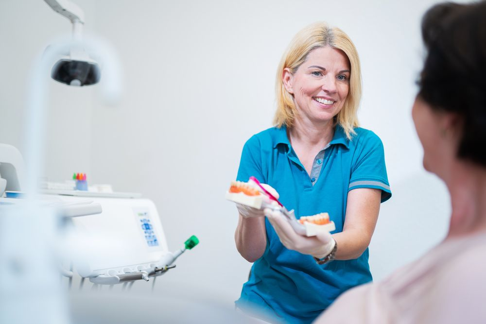 Unser Zahnarztpersonal zeigt einer Patientin bei der zahnmedizinischen Prophylaxe verschiedene Zahnputztechniken.