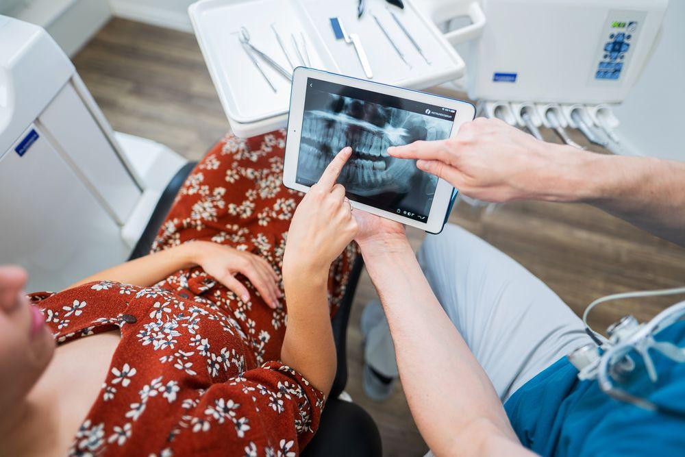 Zahnarzt Dr. Polgart zeigt einer Patientin deren Röntgenbild auf dem iPad.